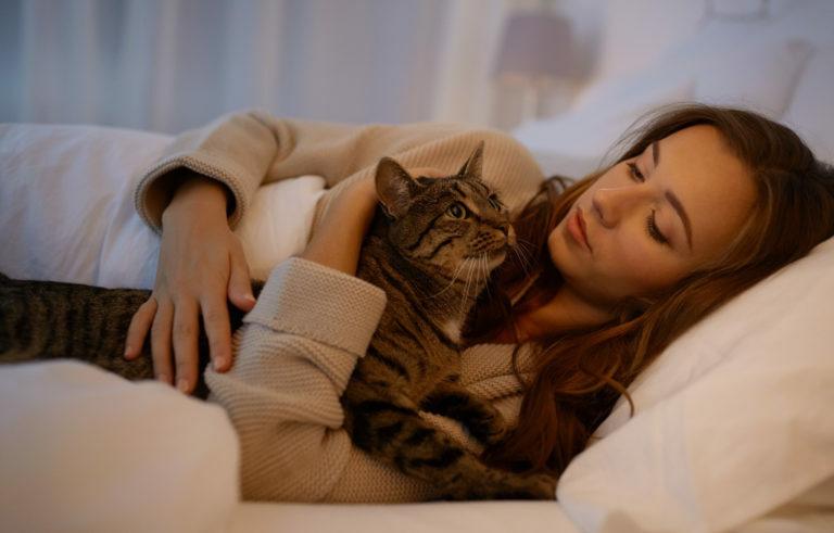šťastná mladá žena s mačkou ležiacou doma v posteli